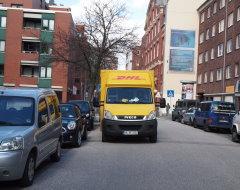 DHL-Paketauto hält in 2. Reihe